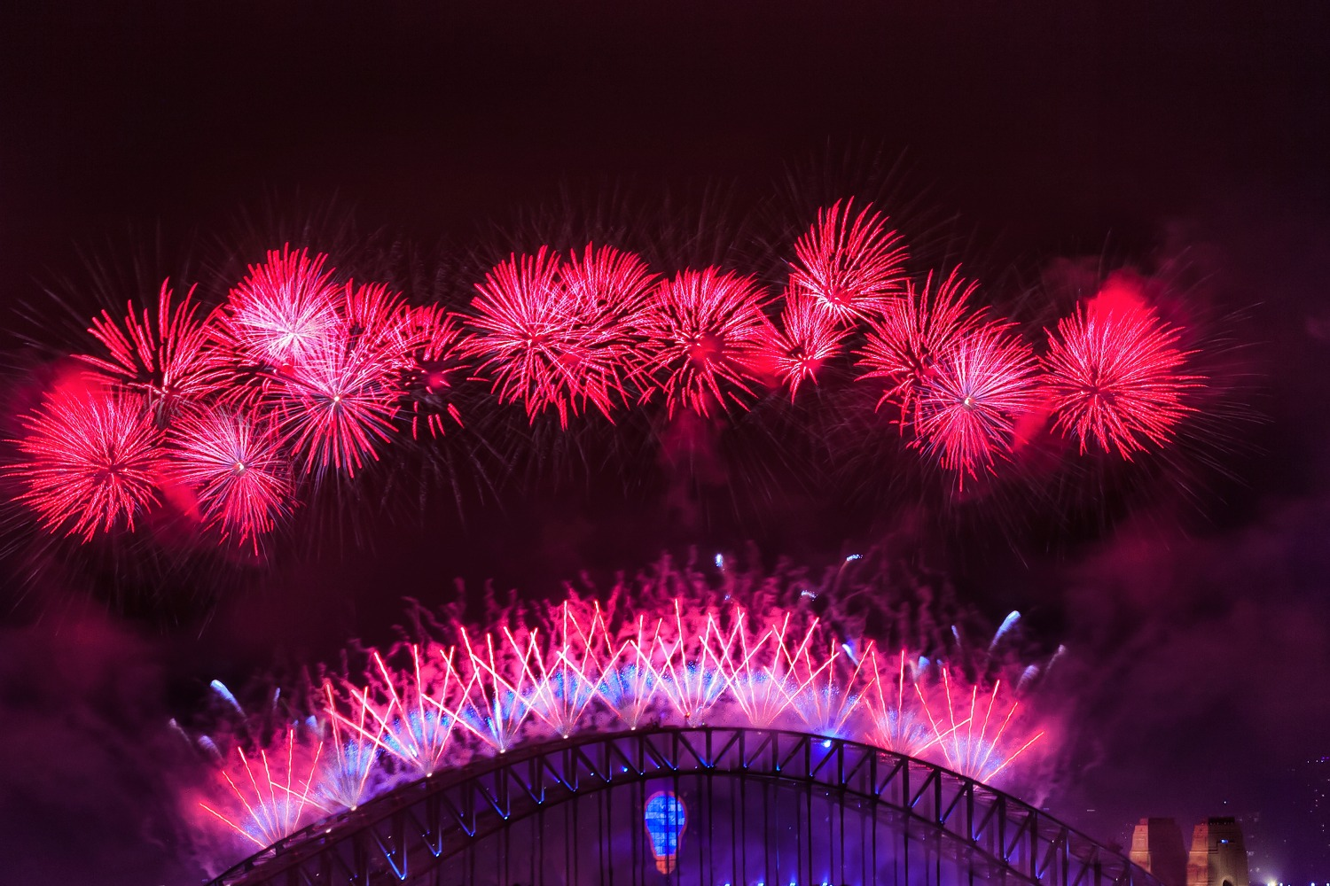 Australia Sydney Harbour bridge arch highlighted by New Year Fireworks bright red light balls and pyrotechnics