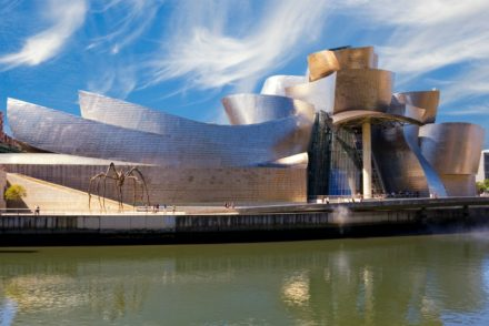 Guggenheim Bilbao museum reflection on the Nervion river, over a cludy blue sky