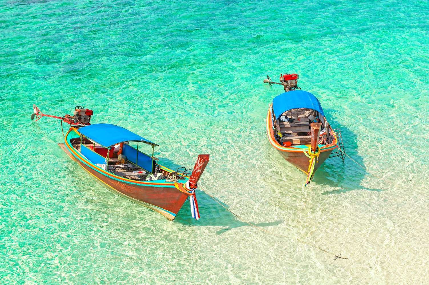 Two anchored boats floating on a shallow water, tropical holidays concept.